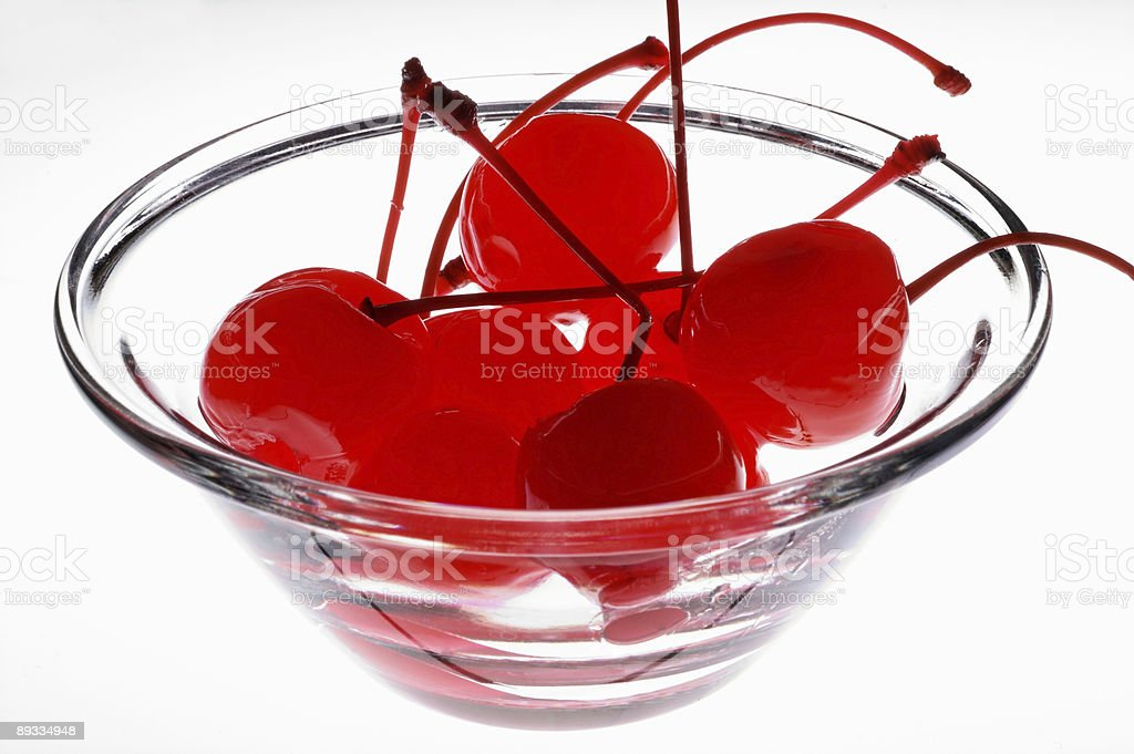 Preserved cherries in a glass cup over light table royalty-free stock photo