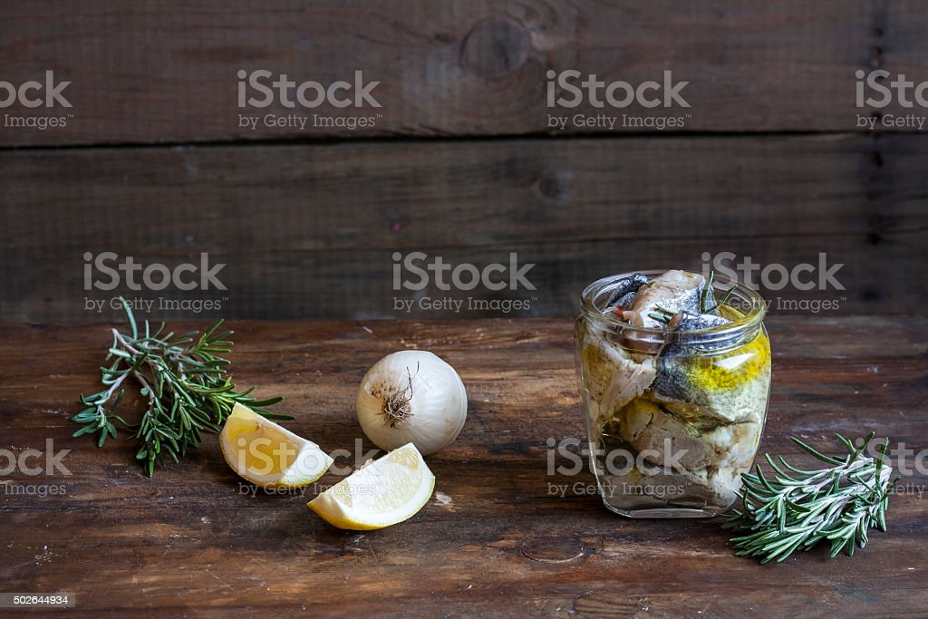 Preserved marinated sliced fish in a glass jar. royalty-free stock photo