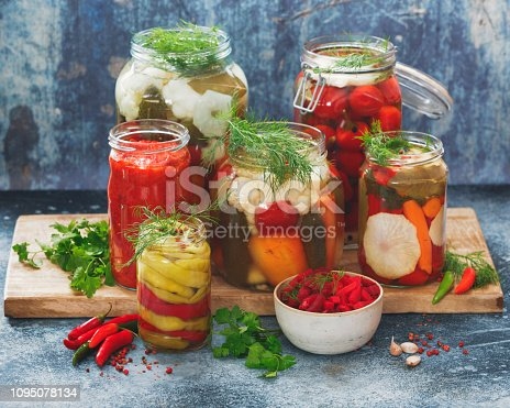 Assorted mixed vegetables in preserving jars on rustic table, selective focus