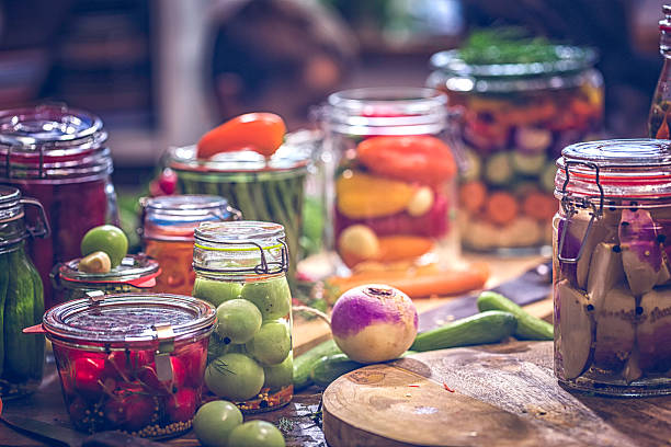 Preserving Organic Vegetables in Jars Preserving organic vegetables in jars like grean beans, garlic, carrots, cucumbers, tomatoes, chilis, paprika and radishes. fermenting stock pictures, royalty-free photos & images