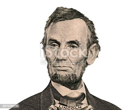 Portrait of former U.S. president Abraham Lincoln as he looks on five dollar bill obverse. Clipping path inside..