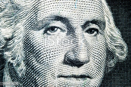 US president George Washington face portrait on the USA one dollar note. Macro shot. Background of the money. George Washington eyes macro shot.
