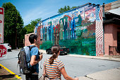 'Washington DC, USA - June 16, 2012: A young man and woman walk past a mural of several U.S. Presidents (from Eisenhower to Obama), painted on the wall of Mama Ayesha's restaurant in the Adams Morgan area of Washington DC.'