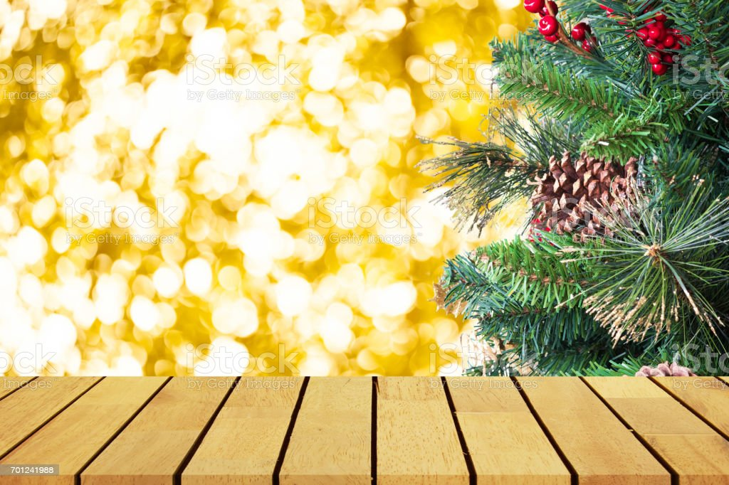 Prespective empty wooden table in front of christmas tree and gole bokeh background, for product display montage or design layout. stock photo
