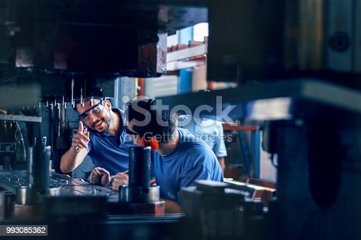 Workers working on the machine for cutting metal sheets