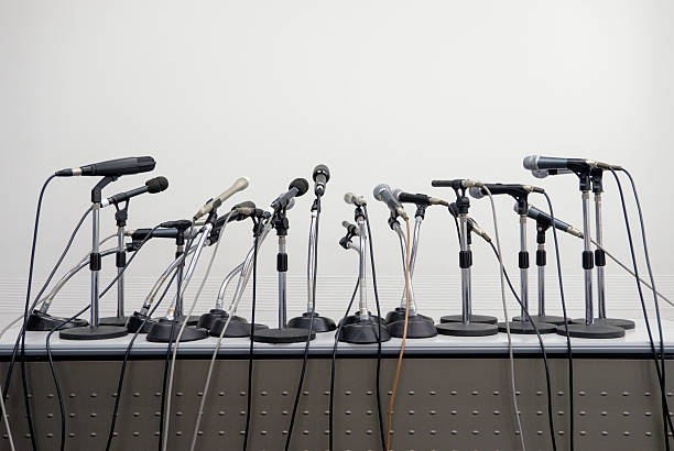 Press Conference Microphone Table A large group of microphones set up on a table for a press conference or public speaking event. press conference stock pictures, royalty-free photos & images
