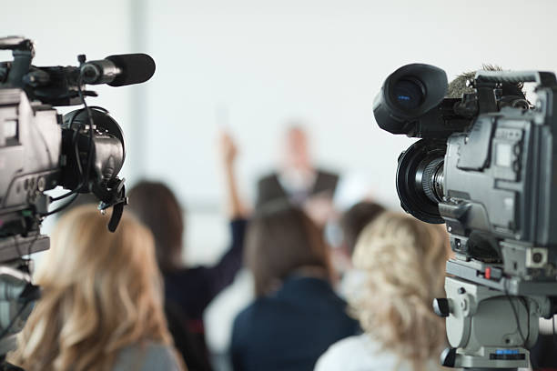 Press conference. Video cameras pointed at businessman or lecturer giving a presentation in background. Focus on cameras.   press conference stock pictures, royalty-free photos & images