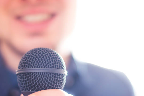 Press officer is speaking into a microphone and giving an interview stock photo