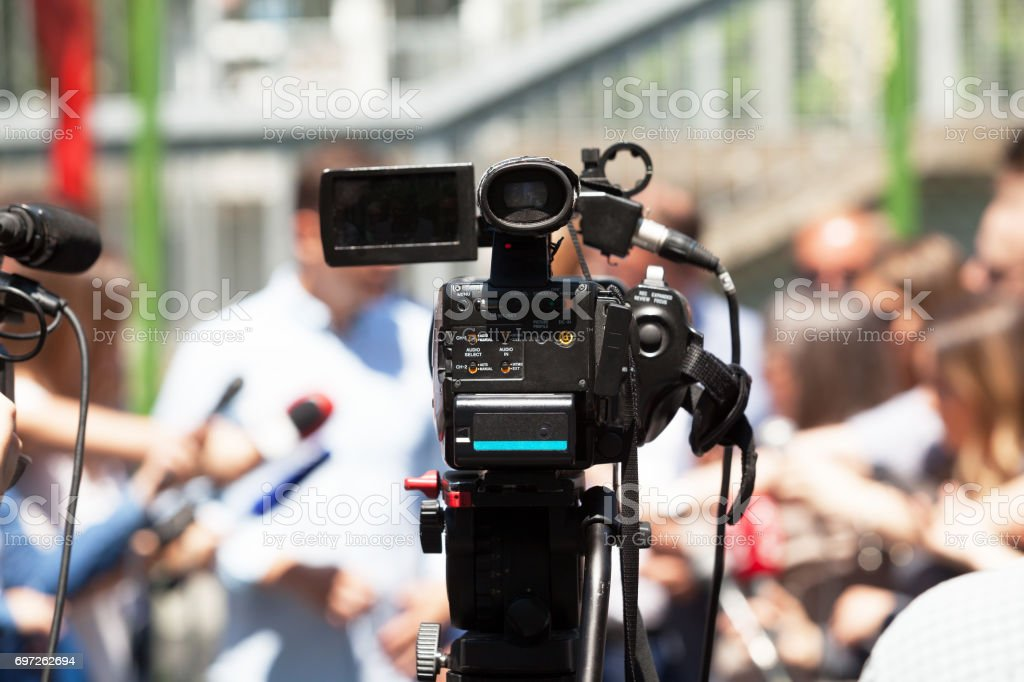 Press or news conference. Filming media event with a video camera. stock photo