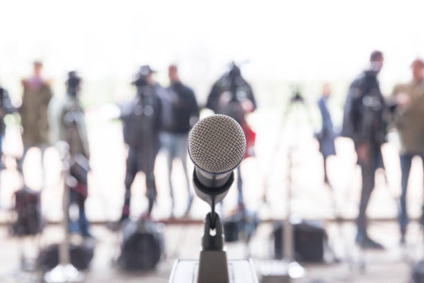 Press or news conference Microphone in focus against blurred camera operators and reporters at press conference press conference stock pictures, royalty-free photos & images