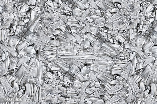 istock pressed aluminum scrap background and texture, silver metal recycling. 1068311526