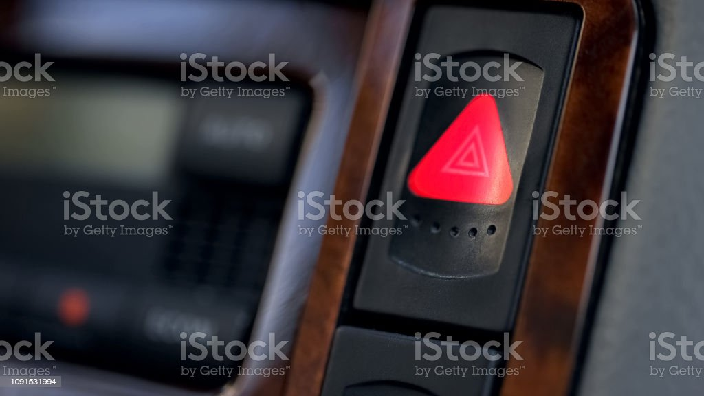 Pressed and glowing emergency car hazard warning flasher button on...