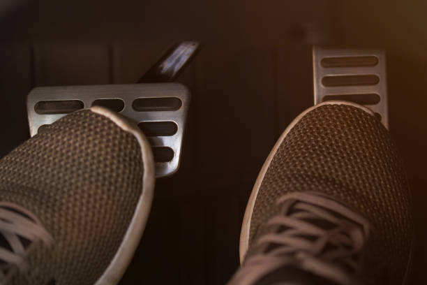 Pressing brake and accelerator pedals stock photo