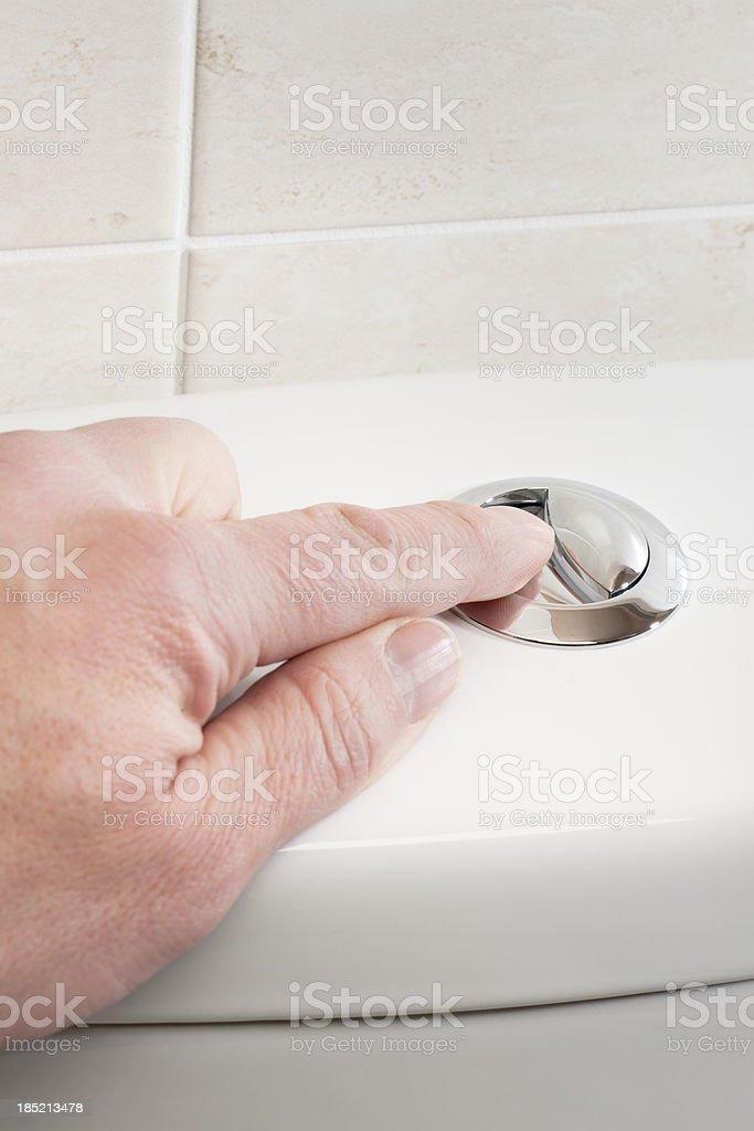 Pressing the button to flush a toilet royalty-free stock photo