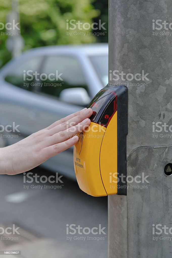 Pressing the yellow crosswalk button royalty-free stock photo