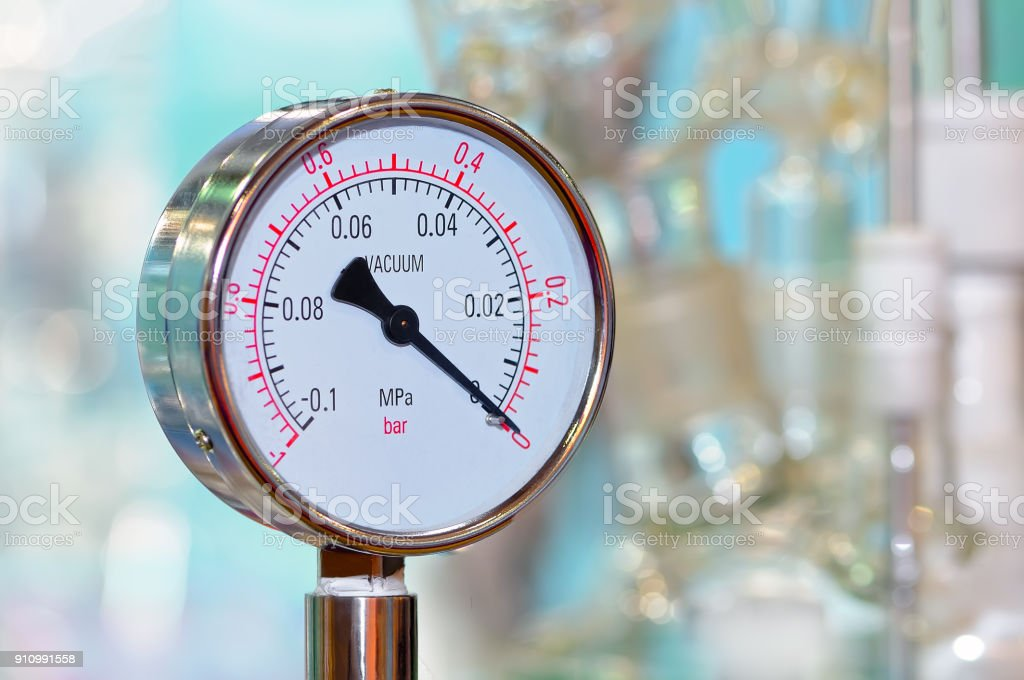Pressure gauge on a blurry industrial background. stock photo