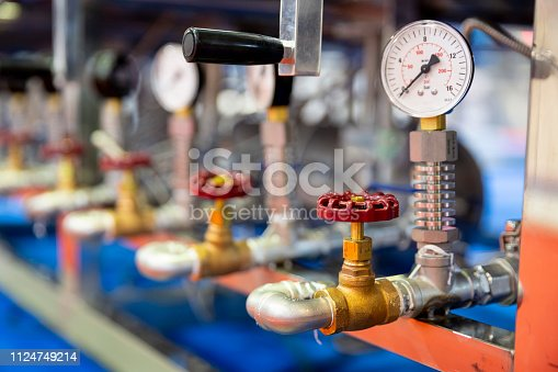 Pressure measuring instrument - bar, psi. Red metal valves on the pipes. Pressure device for industry system.