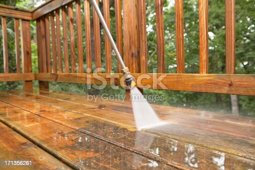 A pressure washer sprayer is cleaning a weathered treated wood deck.
