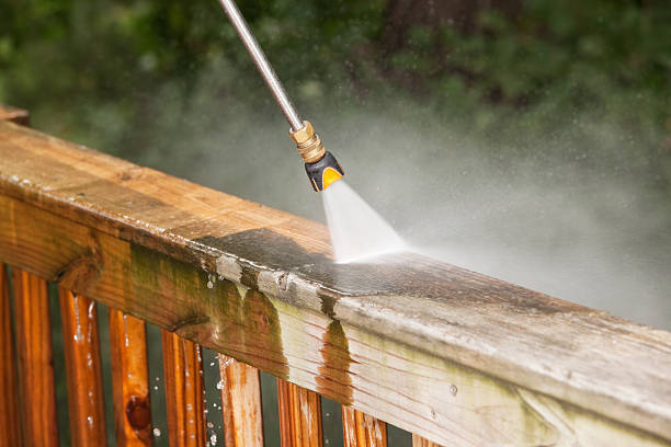 Pressure Washer Cleaning a Weathered Deck Railing stock photo