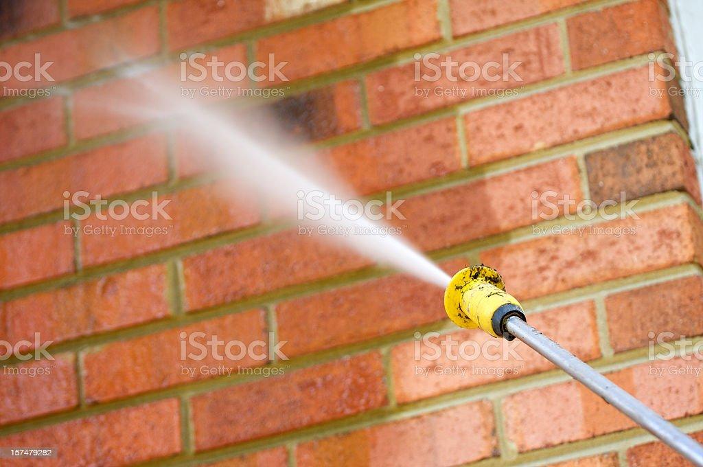 pressure washing a brick wall royalty-free stock photo