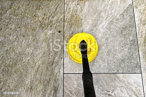 istock Pressure washing porcelain tiles on a garden patio 1313163161