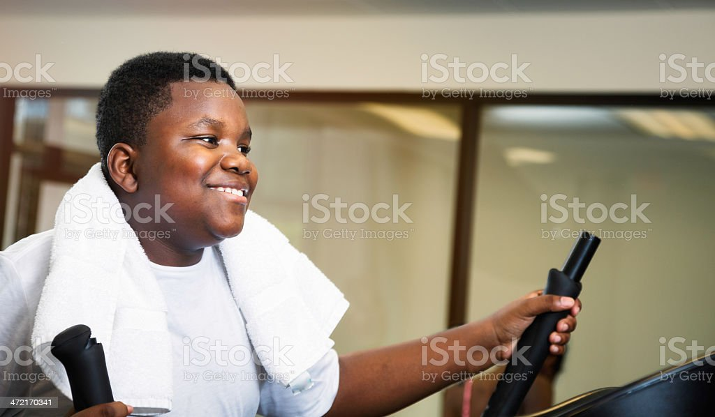 Preteen black boy working out at elliptical machine stock photo