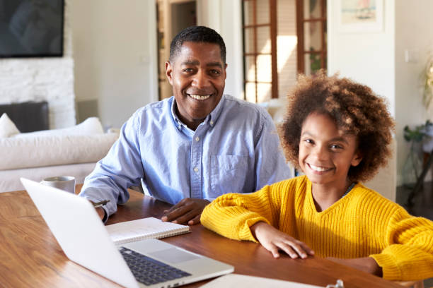 pre-teen black girl and her male home tutor sitting at a table in the dining room smiling to camera, close up - girl study home laptop front imagens e fotografias de stock