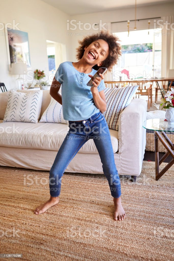Black girl barefoot Preteen Black Girl Singing And Dancing In The Living Room Using A Social Media App On Her Smartphone Full Length Vertical Stock Photo Download Image Now Istock