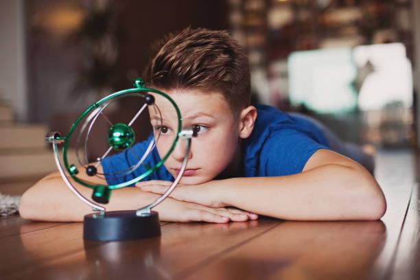 Aprendizagem de menino pré-adolescente sobre movimento perpétuo - foto de acervo