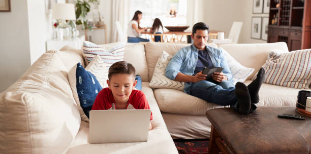 Pre-teen boy lying on sofa using laptop, dad sitting with tablet, mum and sister in the background Pre-teen boy lying on sofa using laptop, dad sitting with tablet, mum and sister in the background apparatus stock pictures, royalty-free photos & images