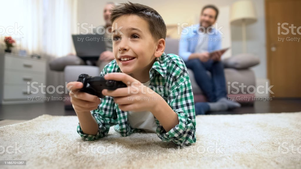 Preteen boy playing video game, dad and granddad smiling, leisure and...