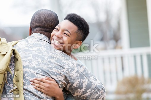 African American preteen boy hugs his dad in the front yard. His dad has return from overseas military assignment.