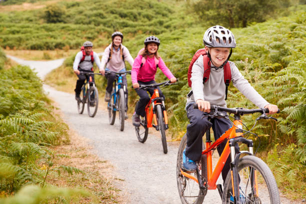 pre-teen boy riding mountain bike with his sister and parents during a family camping trip, close up - ciclismo foto e immagini stock