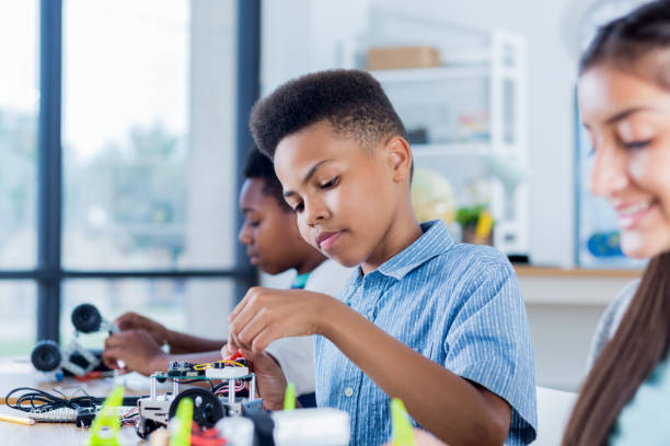 preteen boy works on robotics project at school - tween models stock photos and pictures