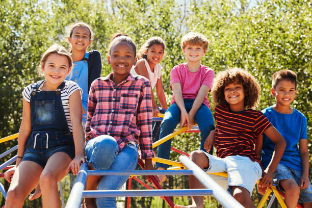 Pre-teen friends sitting on climbing frame in playground stock photo