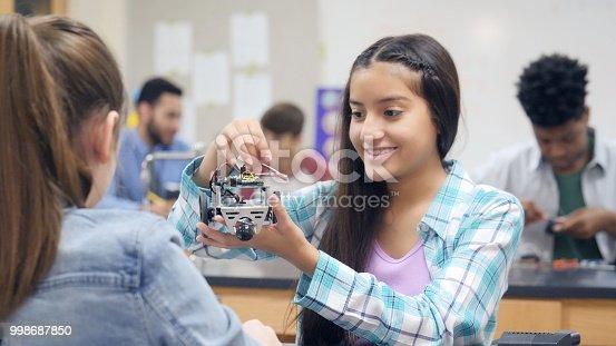 istock Preteen girl adjusts wiring on robotics project at school 998687850