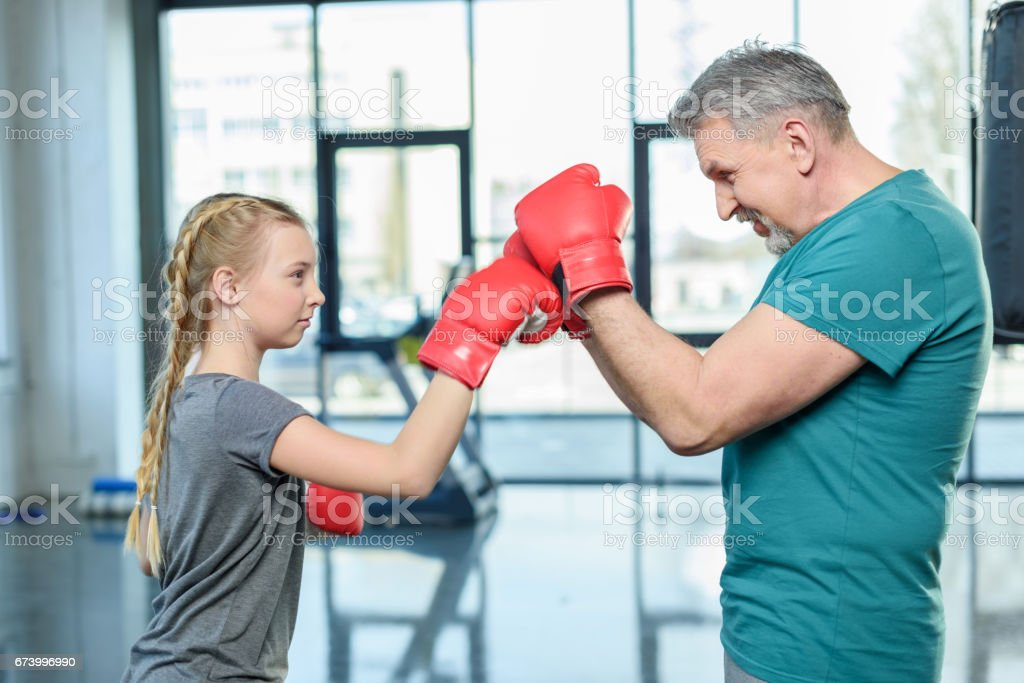preteen girl boxing with senior trainer. Fitness manager, gym class kids concept royalty-free stock photo