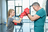 preteen girl boxing with senior trainer. Fitness manager, gym class kids concept