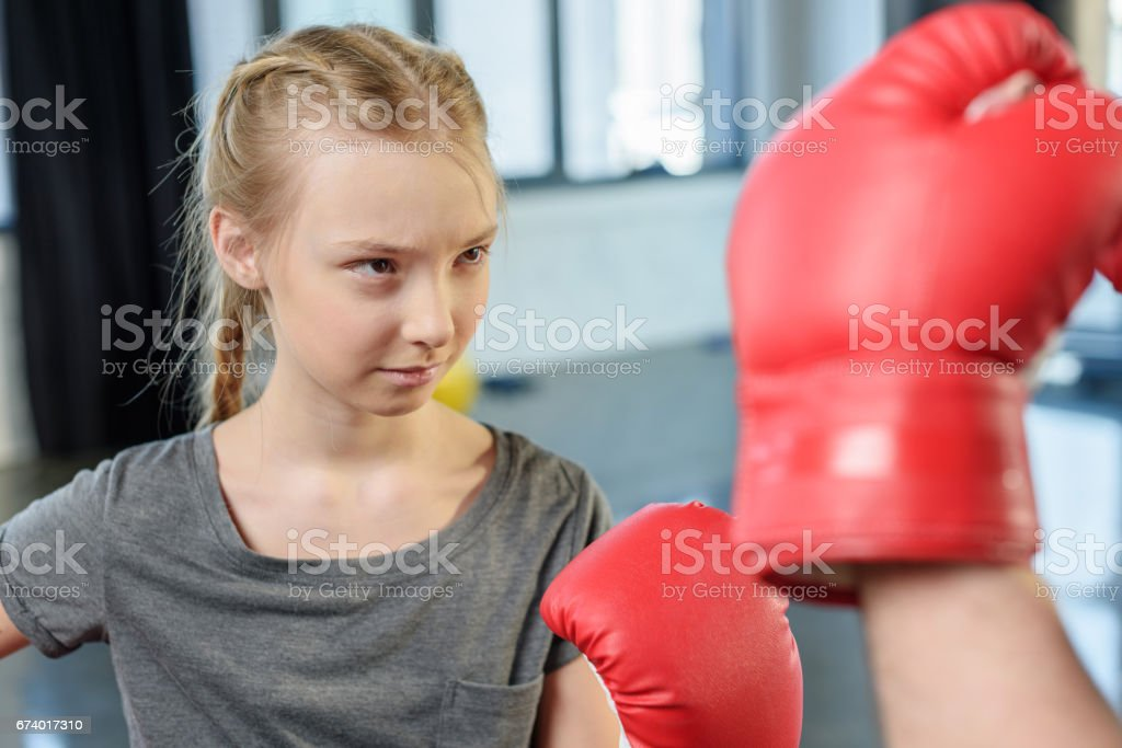 preteen girl boxing with trainer. Fitness manager, gym class kids...