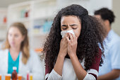 A preteen girl stands in the middle of her local pharmacy and closes her eyes.  She draws a tissue up to her mouth with both hands and coughs.  Her unrecognizable brother stands at the pharmacy counter in the background to purchase cold medication for her.