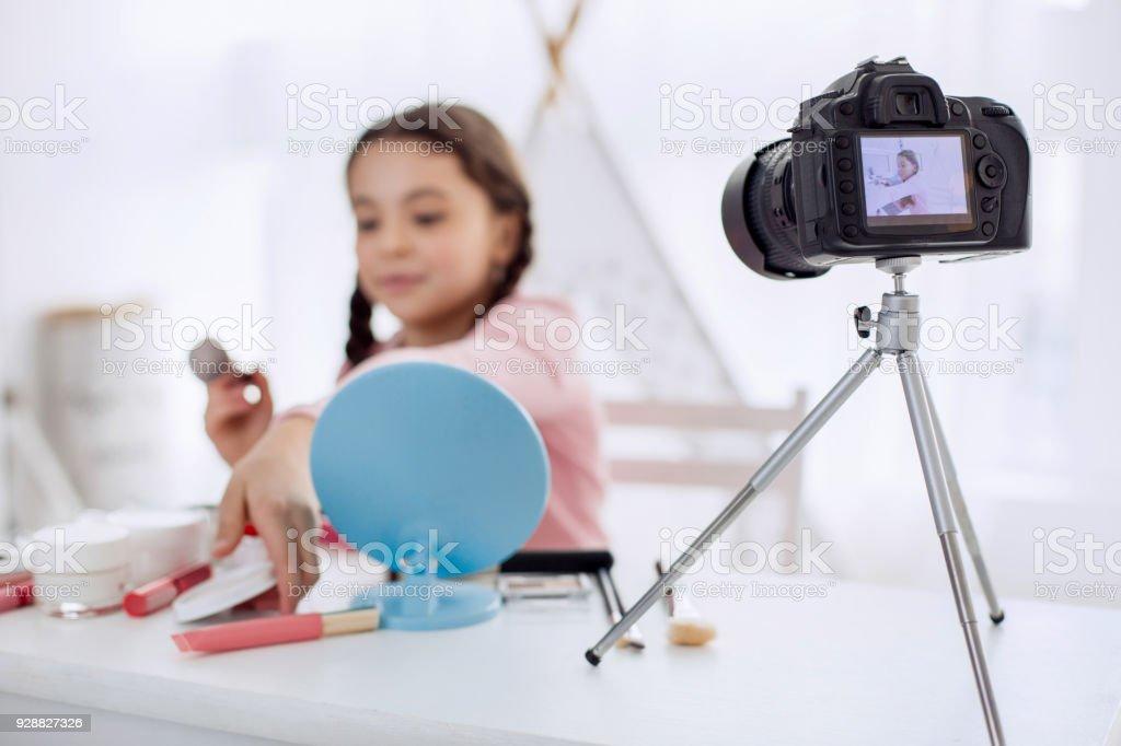 Pre-teen girl filming a makeup tutorial on camera stock photo