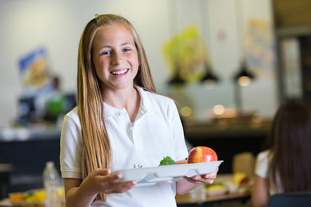 Preteen girl holding tray of cafeteria food in school lunchroom Preteen girl holding tray of cafeteria food in school lunchroom cute middle school girls stock pictures, royalty-free photos & images