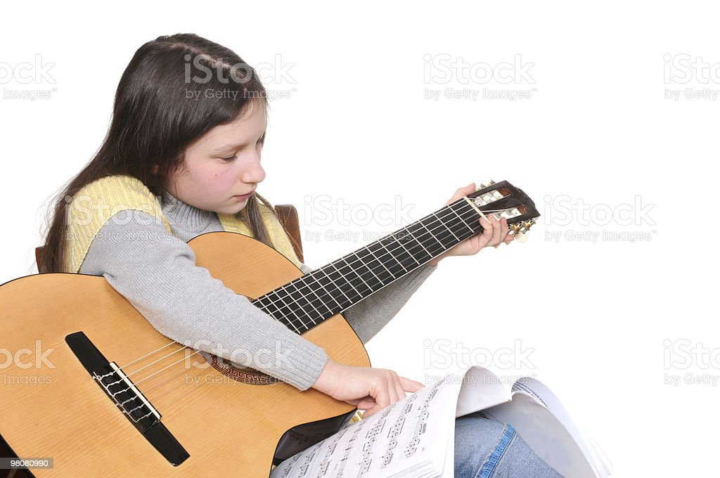 Preteen girl learning to play guitar royalty-free stock photo