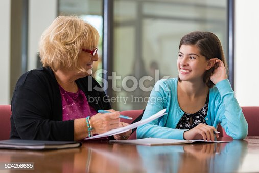 istock Preteen girl meeting with school counselor or therapist 524258665