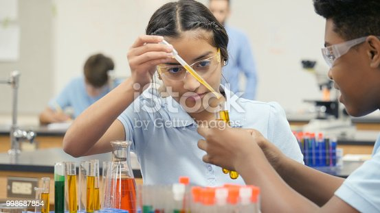 A preteen girl sits at a table in her school science lab with her partner.  He holds up a test tube as she adds more liquid with a dropper.