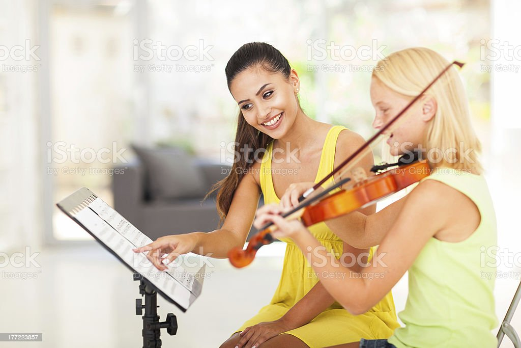 preteen girl play violin under teacher's instructions royalty-free stock photo