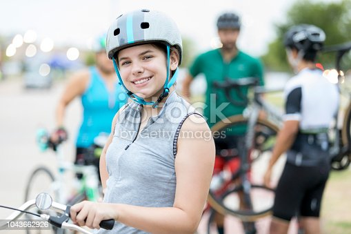 A smiling preteen girl stands beside her bike and smiles for the camera before a bike race for charity.