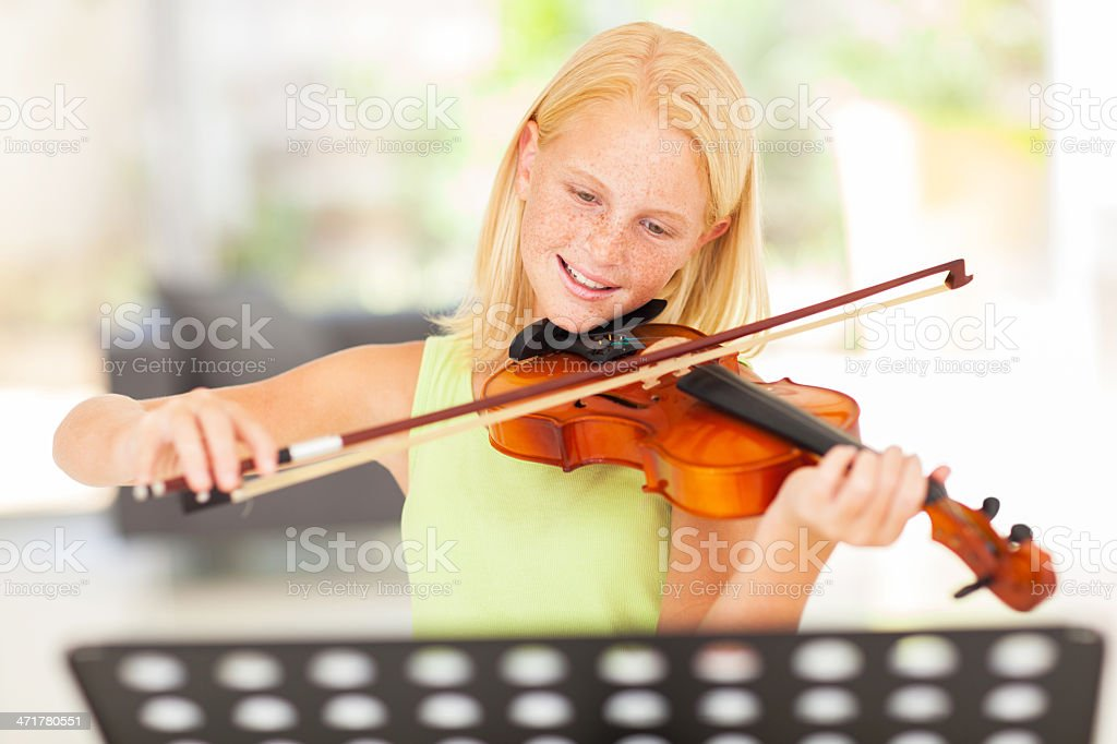 preteen girl practicing violin at home royalty-free stock photo