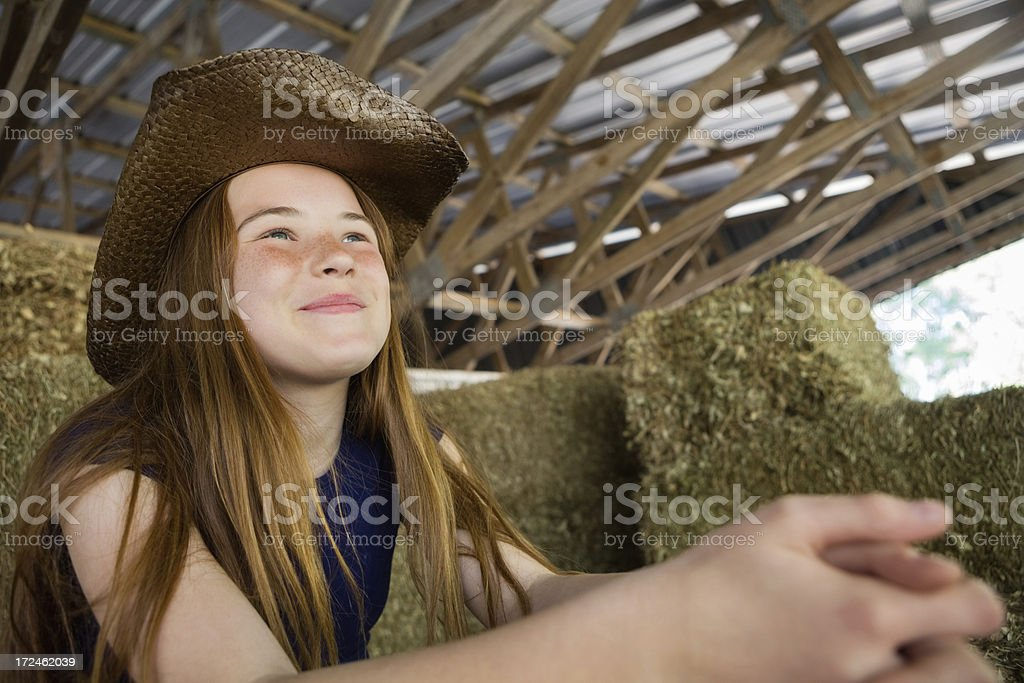 Preteen girl resting after farm chores in hay filled barn royalty-free stock photo