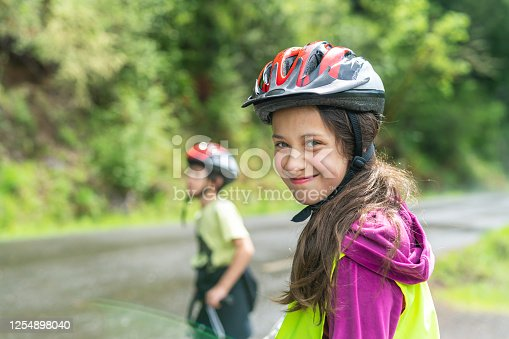 A pre-teen cyclist wearing a yellow safety vest and helmet takes takes a break from riding to smile at the camera. Her little brother is also riding in the background.